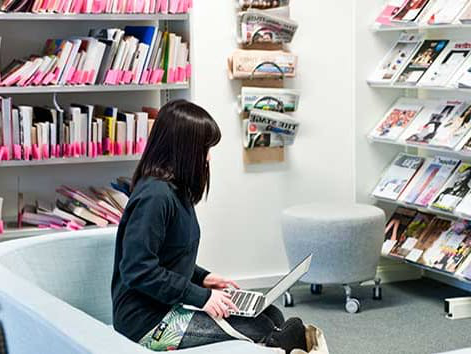 Student in the LCF Library using their laptop