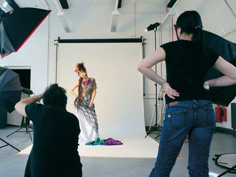 Photography studio with female model in a dress 和 two photographers