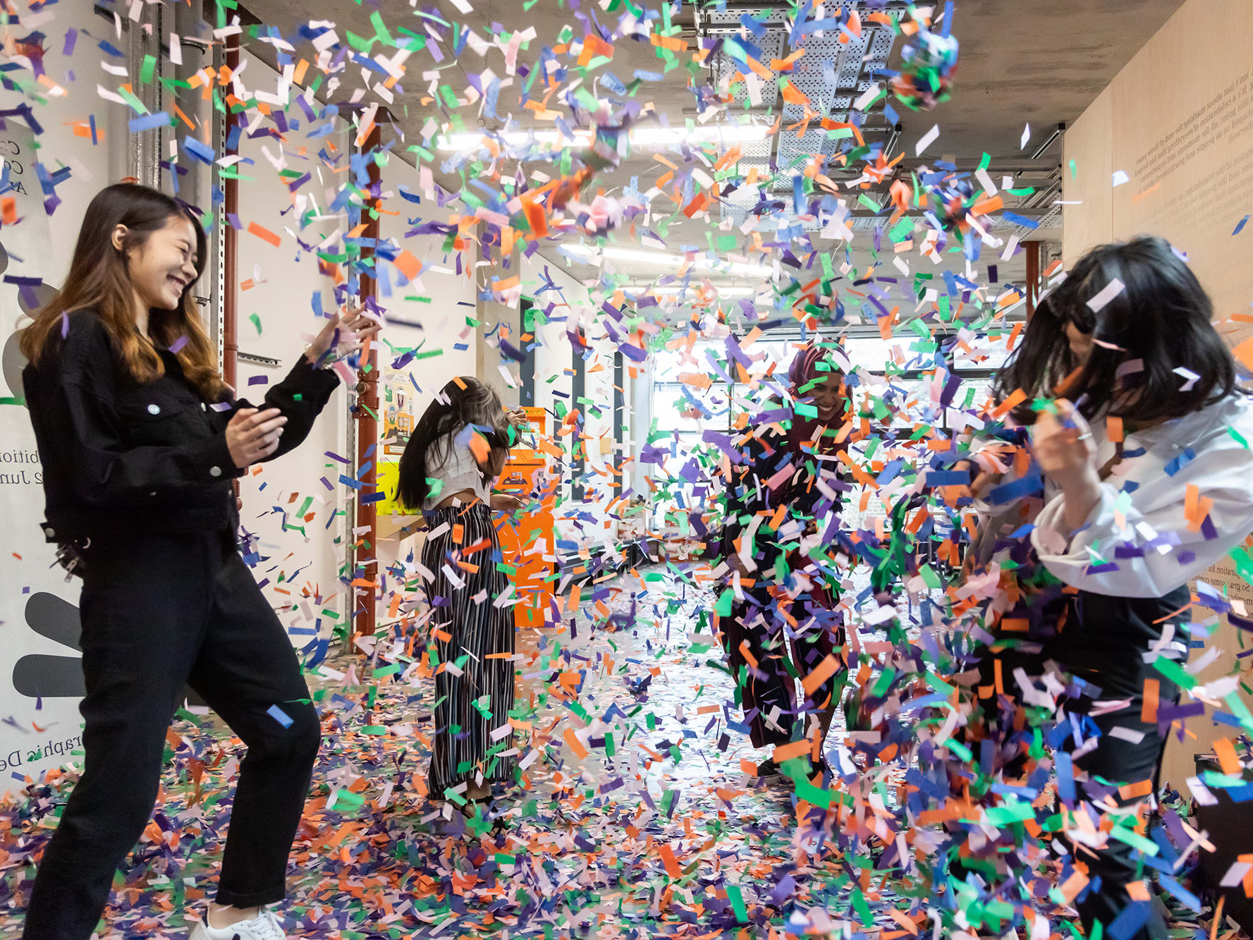 Four students throw green, orange, purple and white confetti at each other at the BA Graphic Design Summer Show at 坎伯韦尔