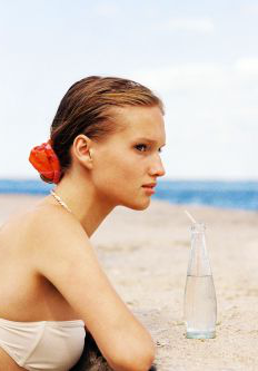 Woman resting her arms on a rock with a glass bottle of water in front of her