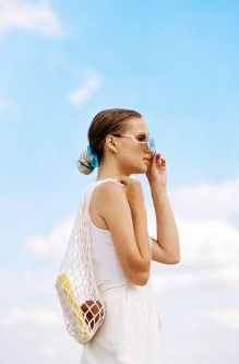 Woman with a mesh bag over one shoulder sliding her sunglasses down her nose