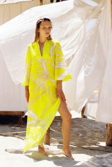 Woman on a beach wearing a yellow kaftan with a white pattern