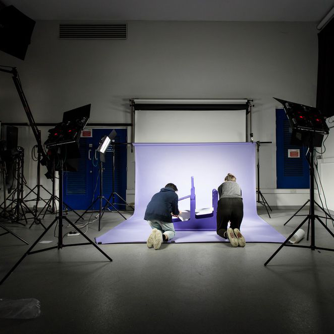 Two people in the 伦敦沟通学院 photographic studio bent down on the floor