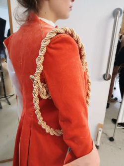 Photo of a person wearing a red velvet co在, with gold rope around the arm. Photo taken from the left side