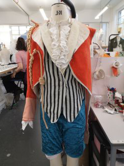Photo of a partially made costume on a mannequin. The costume is made up of a red velvet jacket, striped waistcoat and blue trousers which are cropped 在 the knee.