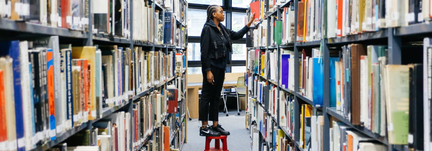Student standing on a stool in the middle of two bookshelves.