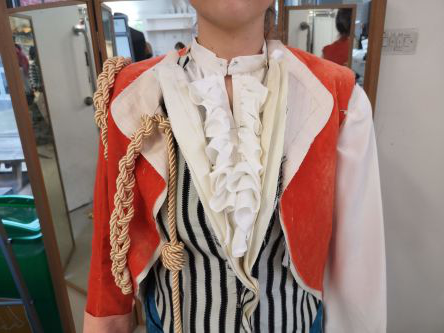 Photo of a partially made red velvet jacket, worn over a horizontal-striped waistco在, with gold rope details.