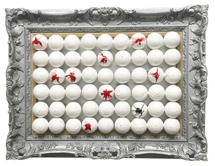 Daniela's artwork called Mirror Mirror. A silver carved frame with rows of white ping pong balls, some with red paint, and one with black paint marked on.